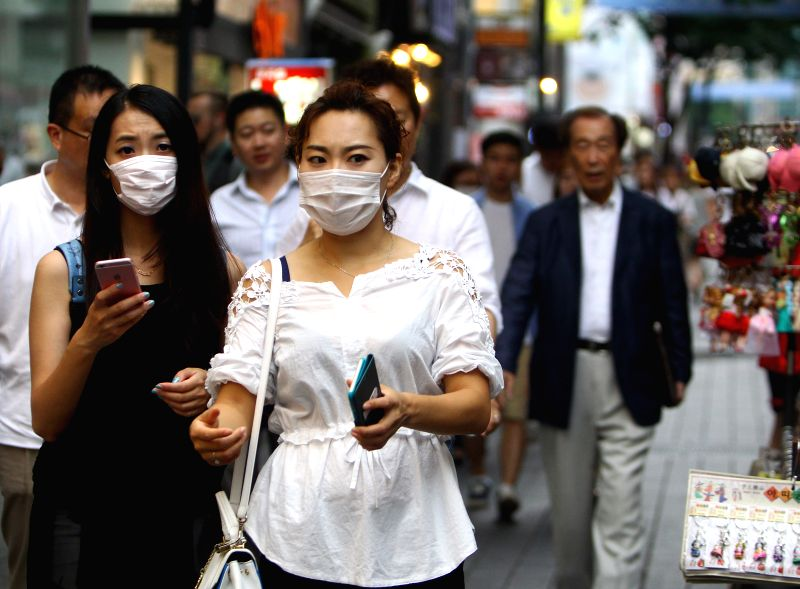 Tourists walk in Myeongdong commercial district in Seoul, South Korea, June 24, 2015. A Chinese female patient, who was infected with MERS in South Korea, recovered ...