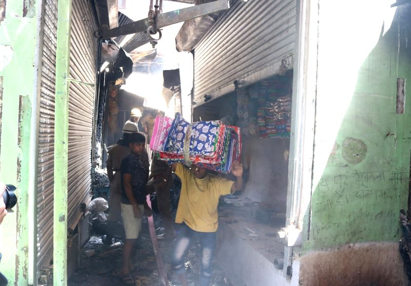 Traders remove their products from shops after a major fire broke out in a cloth shop of a building in Chandni Chowk, Delhi on May 23, 2017.
