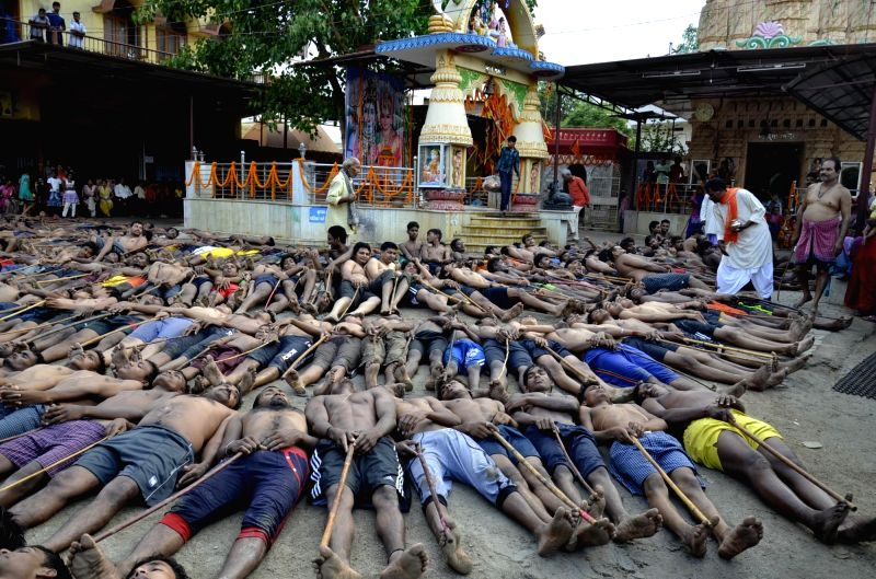 Tribal farmers hold sticks and lie outside the Shiva temple as they wait for blessings from the main priest of the temple during the Manda Festival on the outskirts of Ranchi on May 21, 2016.
