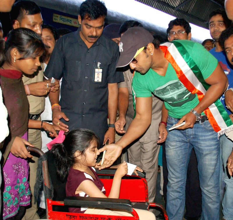 Trinamool Congress candidate for 2014 Lok Sabha Election from Ghatal constituency, actor Dev with a child during an election campaign in Malda of West Bengal on April 22, 2014.