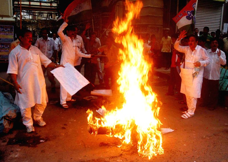 Trinamool Congress (TMC) workers burn an effigy of Prime Minister Narendra Modi in front of Eastern Railway Head-quarters as they protest against Rail budget 2014-15 in Kolkata on July 9, 2014. - Narendra Modi