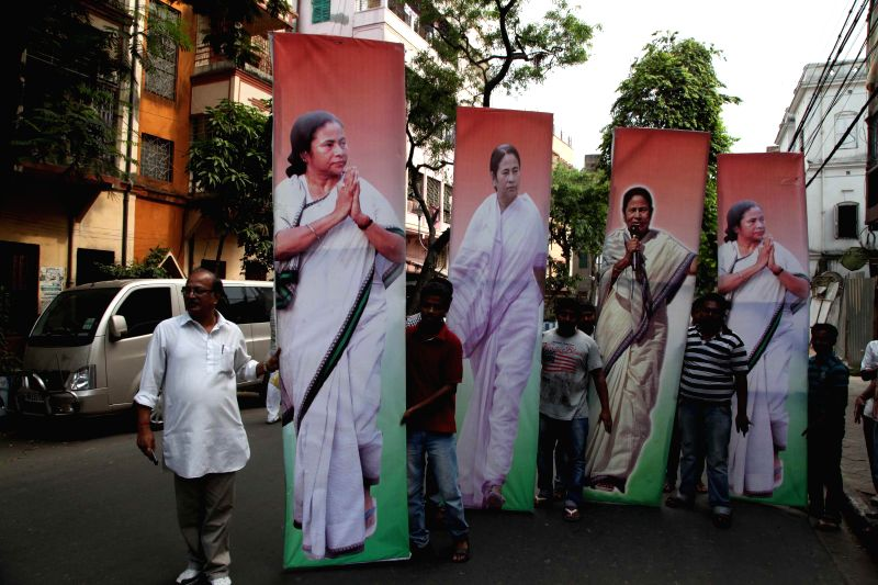 Trinamool Congress workers carry cut-outs of West Bengal Chief Minister and Trinamool Congress supremo Mamata Banerjee in Kolkata on April 11, 2014.