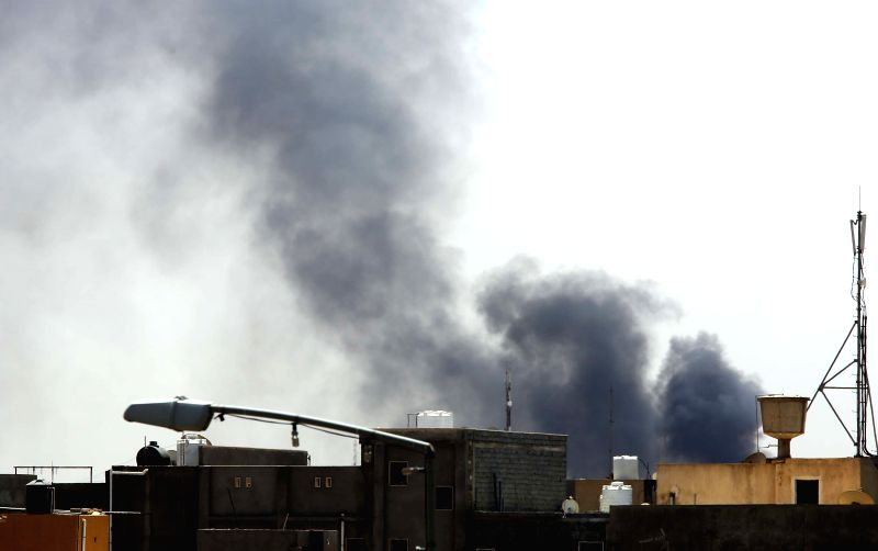 Dark smoke rises from a petrol depot in the outskirts of Tripoli, Libya, on Aug 14, 2014. Clashes between rival militias intensified in Libya's capital city of ...