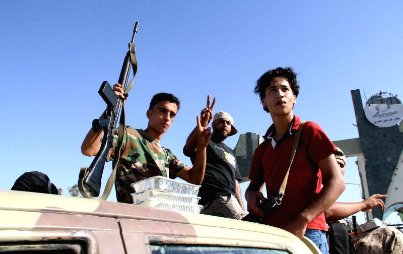 Some Libya Dawn militants pose for photo in a truck mounted with anti-aircraft guns at the gate of Tripoli International Airport, in Libya, on Aug. 24, 2014. ...