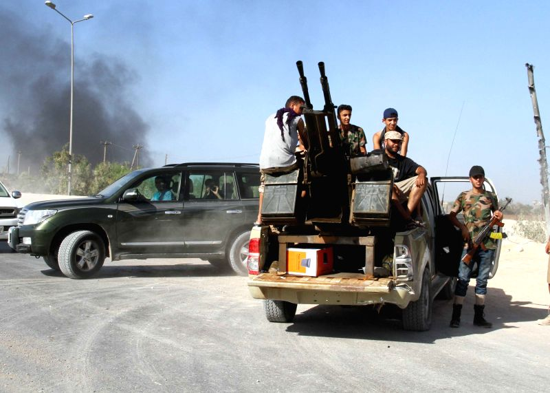 Some Libya Dawn militants sit in a truck mounted with anti-aircraft guns at the gate of Tripoli International Airport, in Libya, on Aug. 24, 2014. Libya's ...