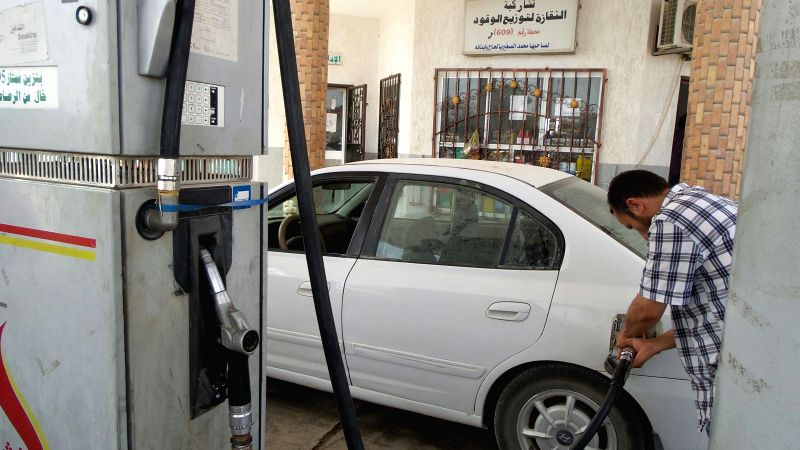 A man fills his car at a petrol station in the city of Al-Khums, about 100 kilometers east of Libyan capital Tripoli, Aug. 5, 2014. Rockets fired by fighting rival ..