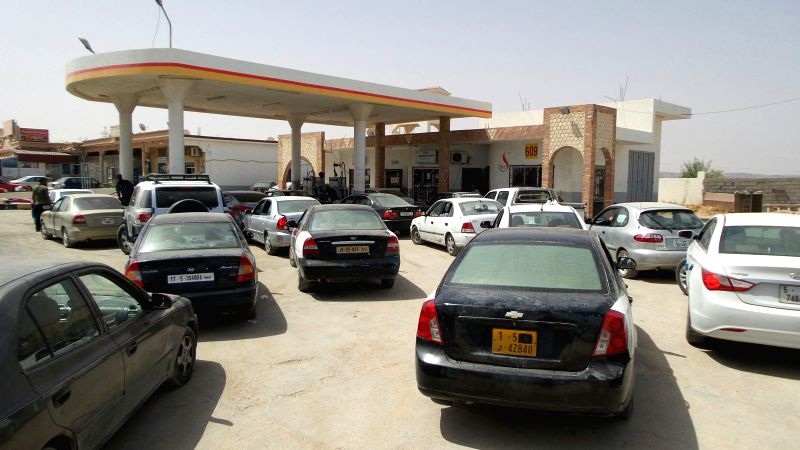 Cars wait in a long queue outside of a petrol station in the city of Al-Khums, about 100 kilometers east of Libyan capital Tripoli, Aug. 5, 2014. Rockets fired by ...