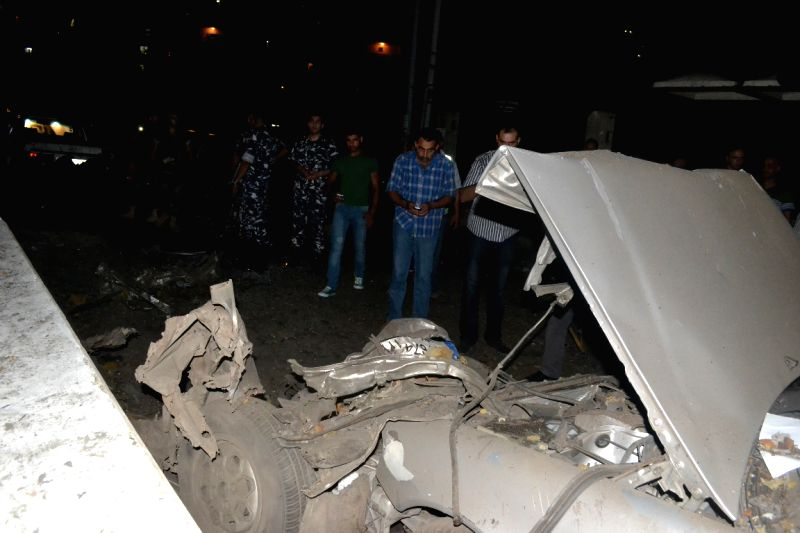 People gather at the site of a car bomb blast in Tripoli, a port city in north Lebanon, on Aug. 6, 2014. A bomb exploded at an army checkpoint in Tripoli on ...