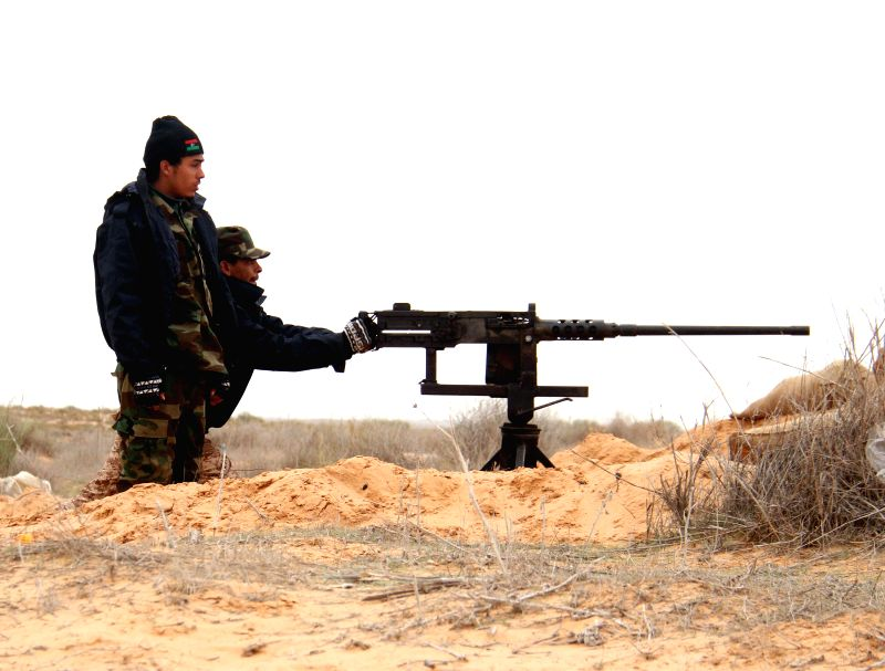 A Libya Dawn fighter aims his weapon during clashes with pro-government forces near Wetia airbase, Libya, on Dec. 29, 2014. Clashes continued between Libya Dawn ...