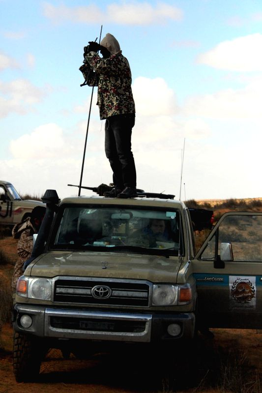 A Libya Dawn fighter stands on a military truck and watches through a telescope near Wetia airbase, Libya, on Dec. 30, 2014. Libyan government forces on Tuesday ...