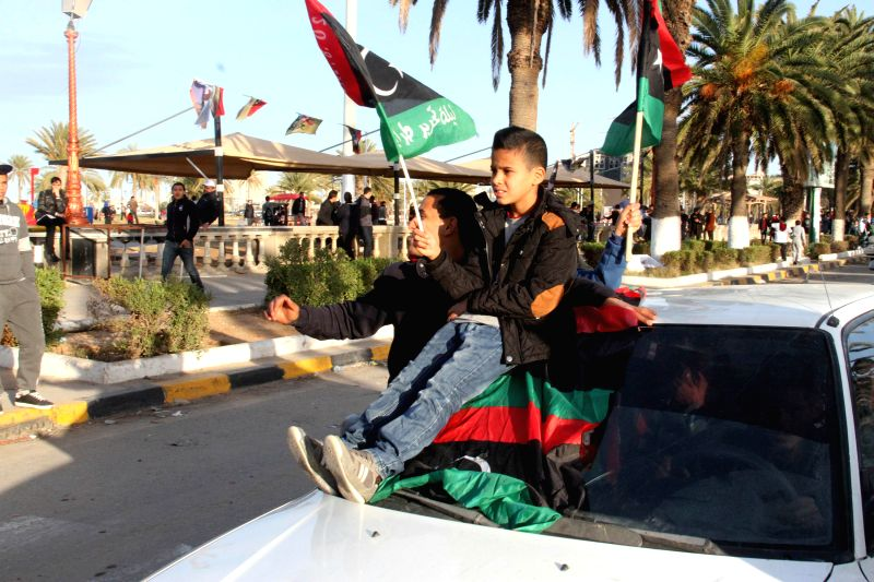 People chant slogans and wave national flags on Martyrs Square in Tripoli, Libya, on Feb. 25, 2015. Citizens on Wednesday celebrated the fourth anniversary of a ...