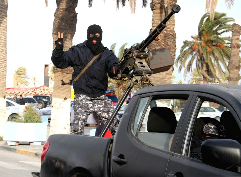 A masked soldier poses for photo on an armored vehicle mounted with an anti-aircraft gun in Tripoli, Libya on Feb. 9, 2015. Police and army forces for Libya's ...