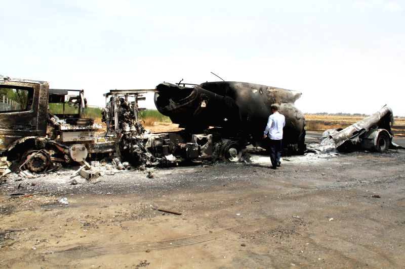 A man checks the burnt oil-tank truck in Tripoli International Airport on July 14, 2014, in Tripoli, Libya. Armed clashes broke out at Libya's international airport