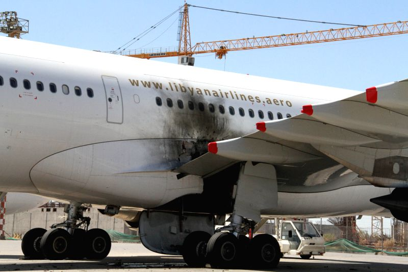 The photo taken on July 16, 2014 shows a damaged plane on the tarmac in Tripoli International Airport, in Libya. Libya's international airport in capital Tripoli ...