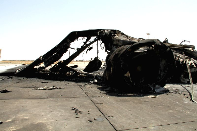 The picture taken on July 21, 2014 shows the wreckage of a plane at Tripoli International Airport, Libya. The airport has been under constant attack by Islamist ...