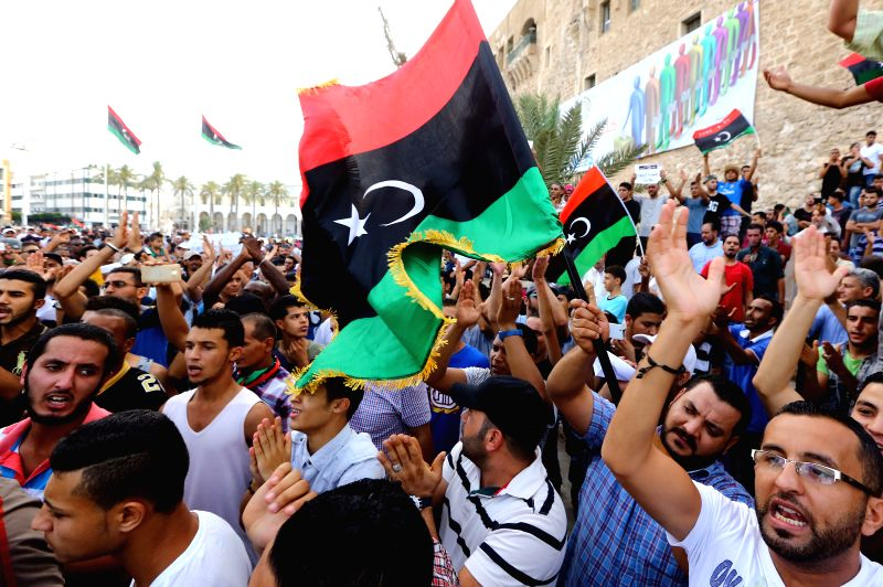 Local citizens wave flags and chant slogans in the streets in Tripoli, Libya on July 31, 2014. Hundreds of people took to the street on Thursday demanding an end of