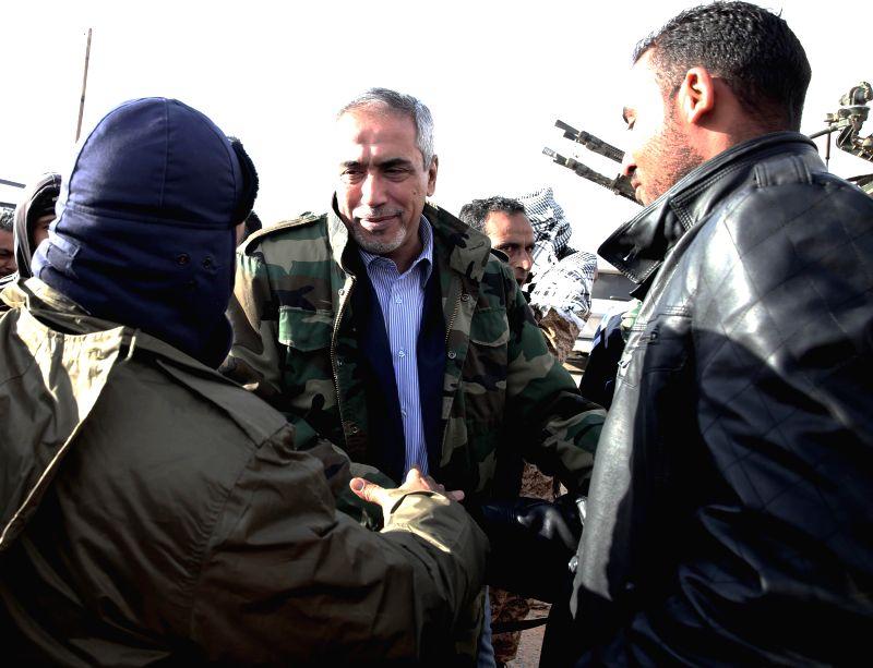 Tripoli (Libya): Libya's Islamist-backed Prime Minister Omar al-Hasi (C) pays a visit to Libya Dawn militants on the front, west of Tripoli, Libya, on Dec. 11, 2014. The Islamist armed alliance Libya - Omar