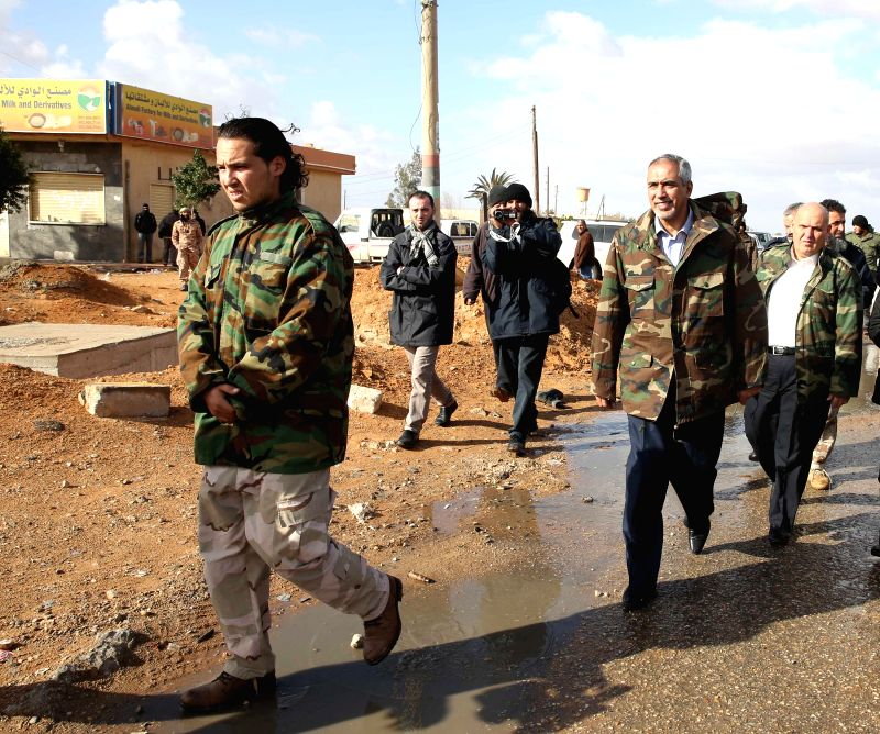 Tripoli (Libya): Libya's Islamist-backed Prime Minister Omar al-Hasi (2nd R) pays a visit to Libya Dawn militants on the front, west of Tripoli, Libya, on Dec. 11, 2014. The Islamist armed alliance .. - Omar