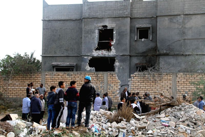 Local citizens stand besides a building damaged in the national army's air strikes in Tripoli, Libya, on Nov. 25, 2014. Libyan national army's warplanes on Monday bombed Mitiga airport in ...
