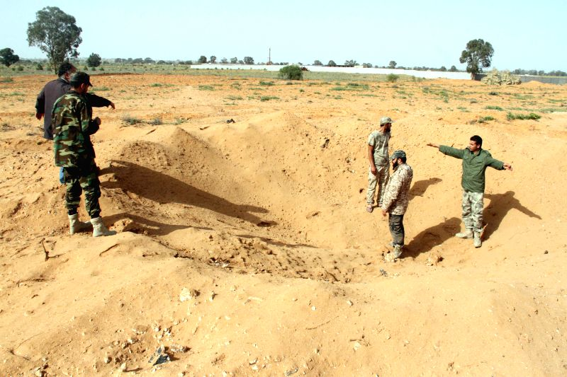 Libya Dawn fighters check a crater left by an air raid in the Tarhuna area, 80 km southeast of Tripoli, Libya, on March 23, 2015. Libyan national army's warplanes ...