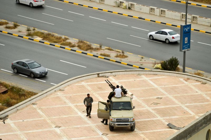 Libyan soldiers stand guard near a road in Tripoli, capital of Libya, on May 18, 2014. Armed clashes happened on Sunday afternoon near Libya's interim parliament ...