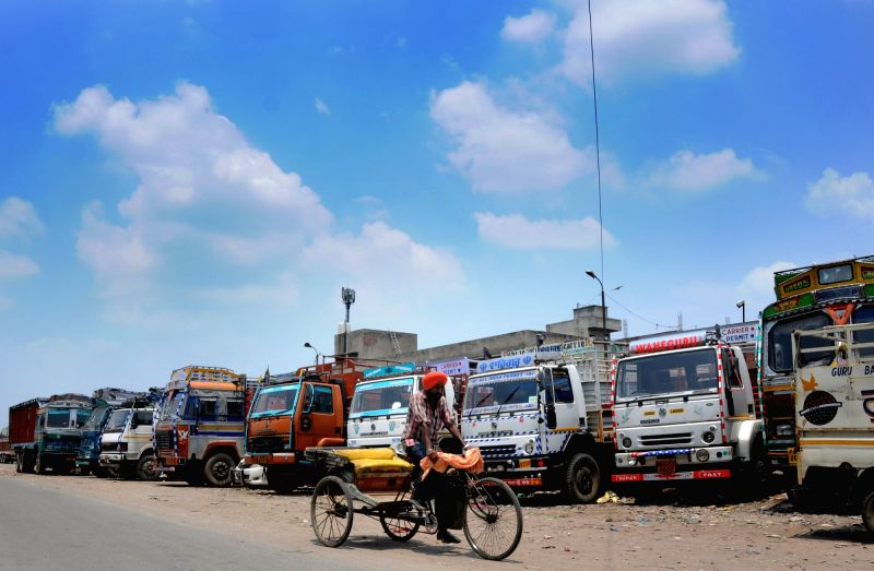 Trucks remain parked at a depot during a nation-wide indefinite strike called by private bus and truck operators to press for their various demands, in Amritsar on July 21, 2018. (Phoo: ...