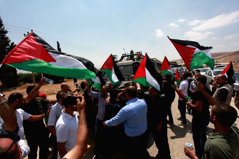 TUBAS, Aug. 6, 2018 - Palestinians wave flags during a protest against the expropriation of their land by Israel in Berdele village near the West Bank town of Tubas, on Aug. 6, 2018.