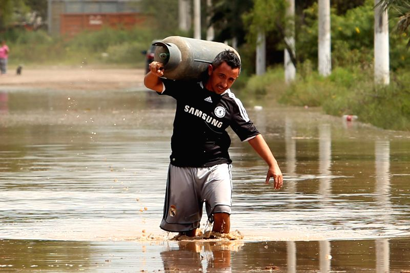 A resident carries a gas tank through a flooded street after being evacuated in Tucuman, Argentina, on April 13, 2015. Several places of Tucuman are in alert as ...