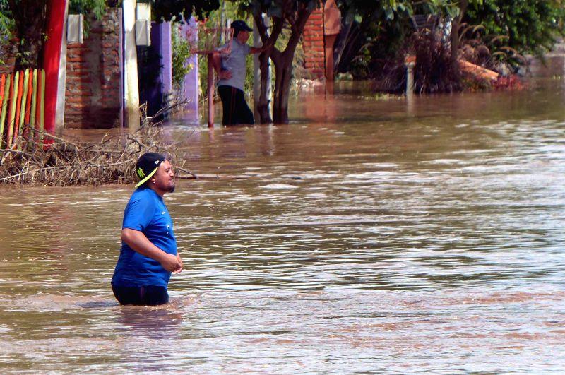 A man walks in a flooded street in Villa de Medinas, Argentina, on March 10, 2015. (Xinhua/Julio Pantoja/TELAM)