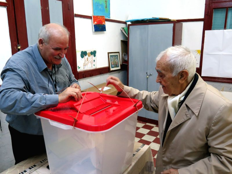 A man (R) casts ballot at a polling station in Tunis, capital of Tunisia, Nov. 23, 2014. Tunisian voters went to polls on Sunday morning to elect the country's first president since the ...