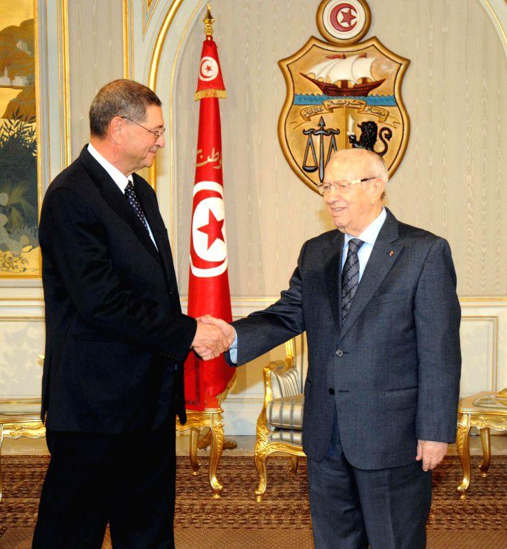 Tunisian prime minister designate Habib Essid(L) shakes hands with Tunisian President Beji Caid Essebsi in Tunisia City, Tunisia, Jan. 5, 2015. The ex-Interior ...