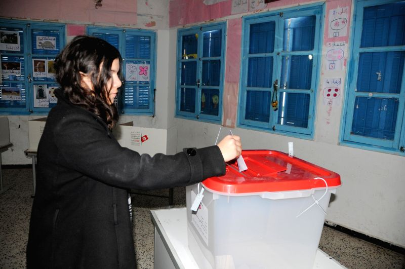 A woman casts her vote for the second round of Tunisian presidential elections in Tunis, Tunisia, Dec. 21, 2014. Polling started in Tunisia on Sunday in a landmark ...