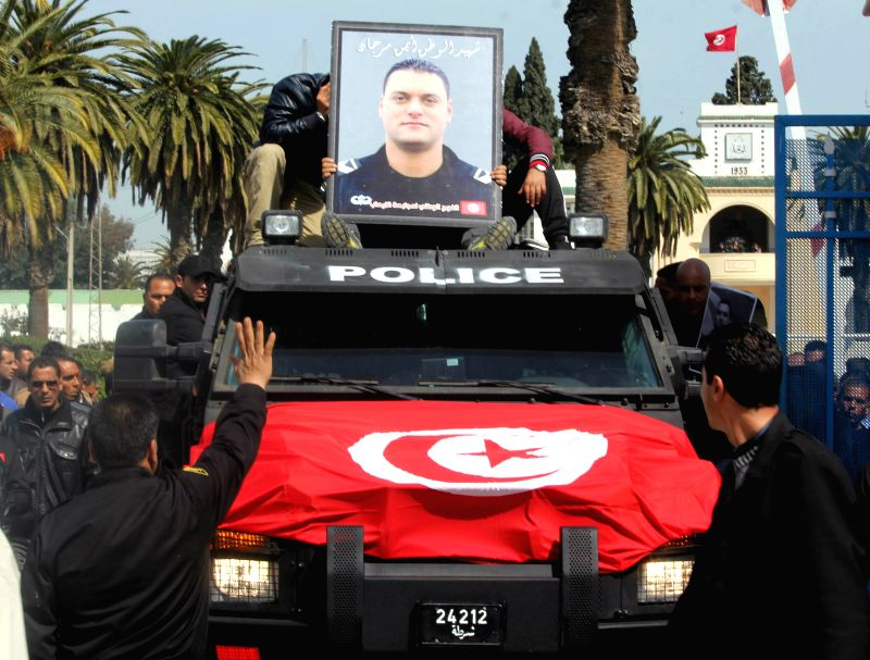 The photo of the police officer Ayman Morgan who was killed in an armed attack on Bardo Museum is placed before his memorial in Tunis of Tunisia on March 19, 2015. ...