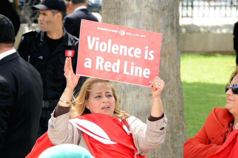A woman holds a placard during the international anti-terrorism march in Tunis, Tunisia, on March 29, 2015. Tunisia held an international anti-terrorism march ...