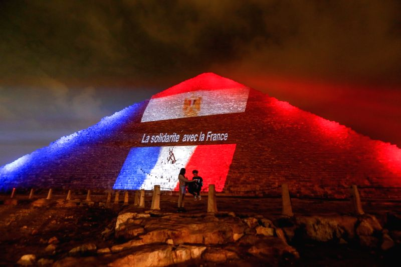 Two Egyptians stay in front of the Great Pyramid of Giza being illuminated with the colors of the French national flag to mourn for the victims of the Paris terrorist ...