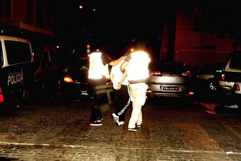 Two policemen (L and R) escort a Spanish man, 29, after he was arrested during a police operation against a network that allegedly attracted and indoctrinated women to send them to combat ...