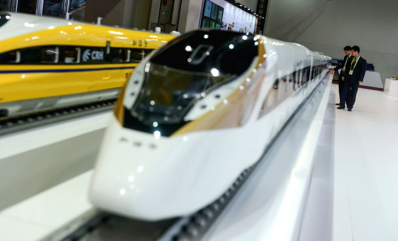 Two visitors look at models of China's standardized electric multiple units at the stand of China Railway during China-Africa Equipment Manufacturing Industry ...