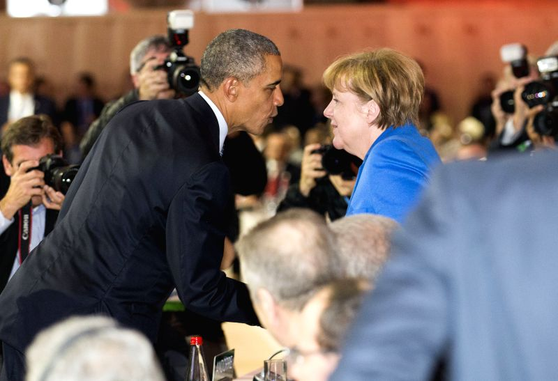 U.S. President Barack Obama (L) greets German Chancellor Angela Merkel after delivering a speech during the 21st Conference of the Parties to the United Nations ...