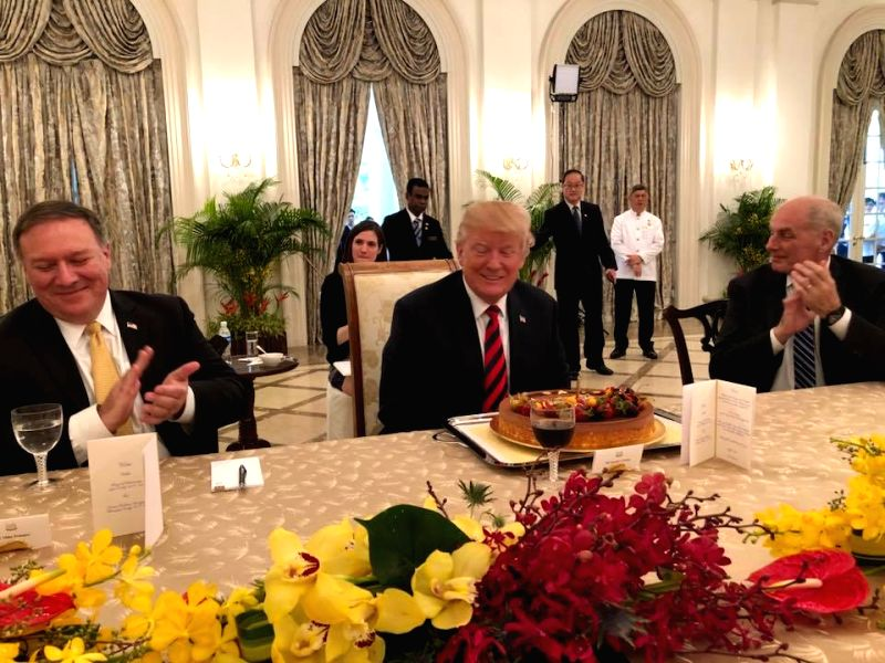 U.S. President Donald Trump (C) smiles as he gets a birthday cake from Singapore's Prime Minister Lee Hsien Loong during a luncheon meeting at Istana Palace in Singapore on June 11, 2018, ... - Lee Hsien Loong