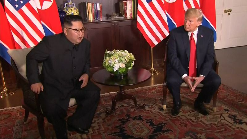 U.S. President Donald Trump speaks with North Korean leader Kim Jong-un before their historic summit at the Capella Hotel in Singapore on June 12, 2018, in this photo capture from Yonhap ...