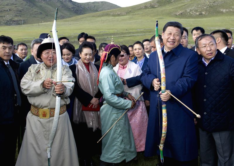"Chinese President Xi Jinping and Mongolian President Tsakhiagiin Elbegdorj prepare to shoot arrows while they watch ""Nadam Fair "", a traditional ..."