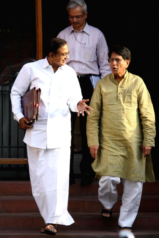Union Finance Minister P Chidambaram and Surface Transport Minister Oscar Fernandes come out after the last cabinet meeting of UPA-II government in New Delhi on May 13, 2014. - P Chidambaram and Fernandes