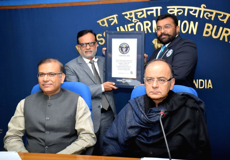 Union Finance Secretary Hasmukh Adhia receives Guinness Book of World Records Certificate from a representative in presence of Union Finance Minister Arun Jaitley and Union MoS Finance Jayant Sinha .. - Arun Jaitley and Jayant Sinha