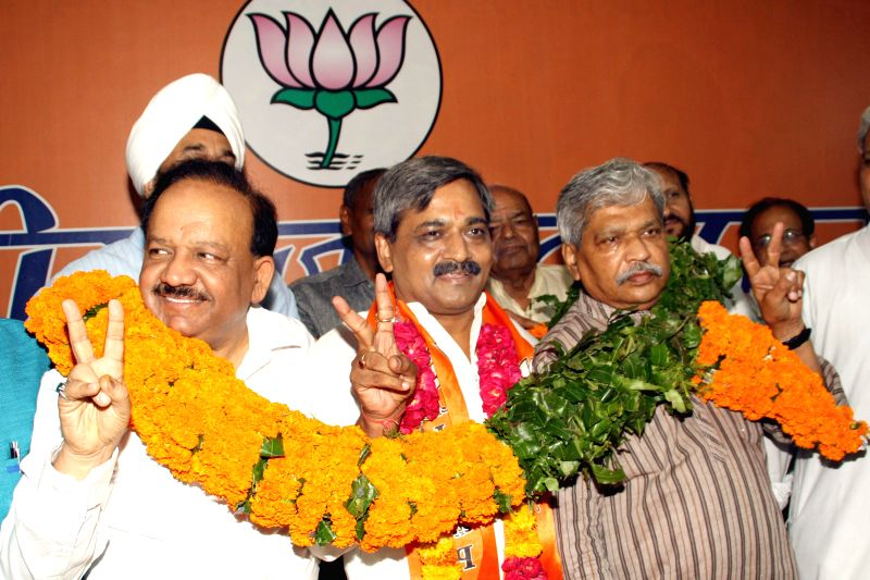 Union Health Minister and former Delhi BJP chief Harsh Vardhan hands over the charge to newly appointed Delhi BJP chief Satish Upadhyay during a programme at BJP office in New Delhi on July 12, 2014. - Satish Upadhyay