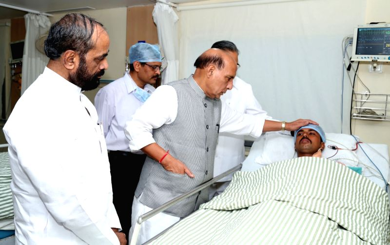 Union Home Minister Rajnath Singh enquires about the health of an injured CRPF personnel at the Ramkrishna Care Hospital, in Raipur, Chhattisgarh on April 25, 2017. Also seen Union MoS Home ... - Rajnath Singh