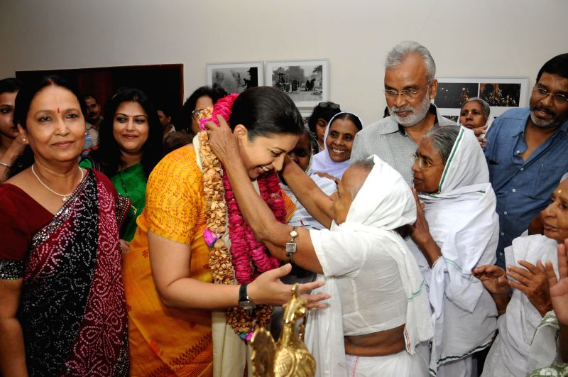 Union HRD Minister Smriti Z Irani with widows of Vrindavan during inauguration of `The Big Picture` - a photo exhibition organised by All india Working News Cameraman's Association at Lalit Kala ... - Smriti Z Irani