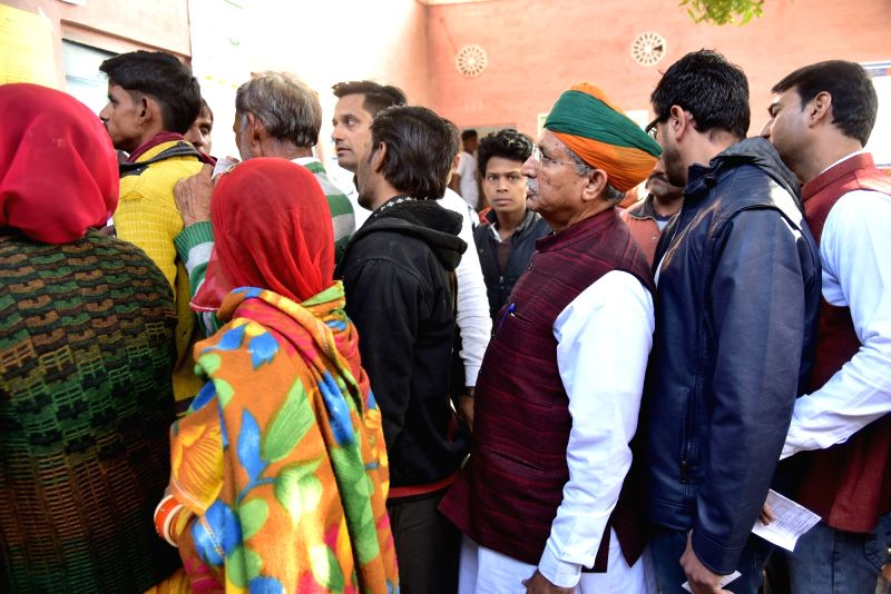 Union Minister Arjun Ram Meghwal waits in a queue along with other voters, to cast his vote for Rajasthan Assembly elections, in Bikaner on Dec 7, 2018. - Arjun Ram Meghwal