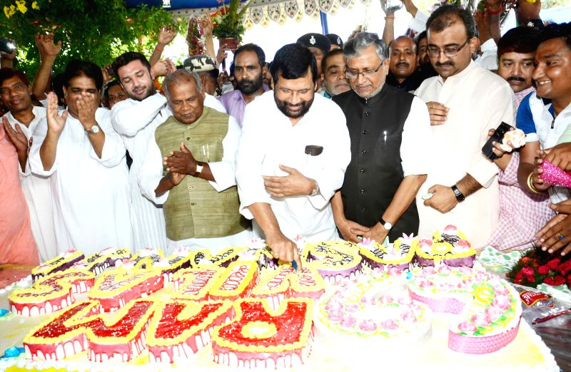 Union Minister for Consumer Affairs, Food and Public Distribution Ramvilas Paswan with his son and Jamui MP Chirag Paswan cuts a cake during a programme organised by his supporters and party ... - Sushil Kumar Modi