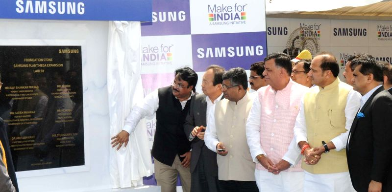 Union Minister for Electronics and Information Technology and Law and Justice Ravi Shankar Prasad unveils the plaque to lay the foundation stone of the Samsung Plant Mega Expansion in Noida, ...