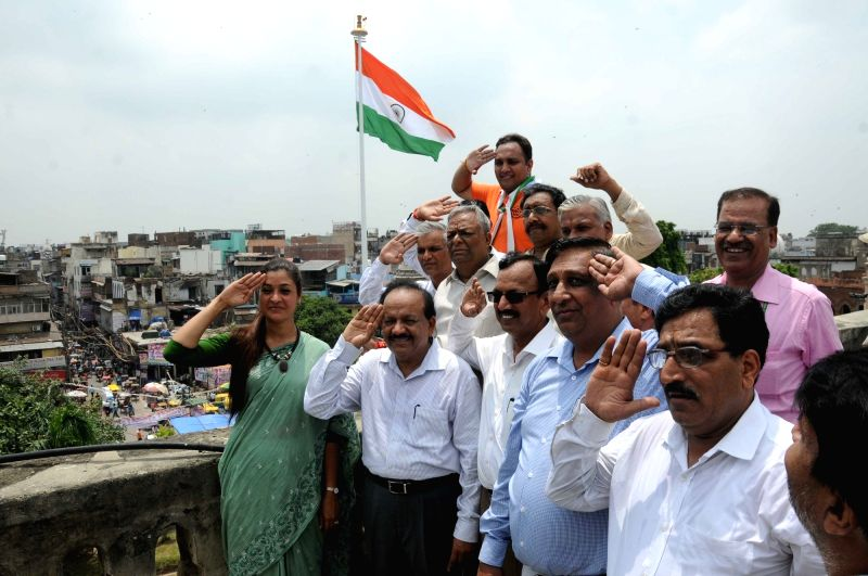 Union Minister for Science and Technology Dr. Harsh Vardhan, AAP legislator Alka Lamba and others pose with national flag hoisted on a 104 feet tall mast -said to be the tallest-  at Town ...
